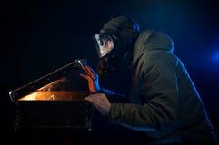 L'uomo nella maschera antigas apre una vecchia valigia Fotografia Stock