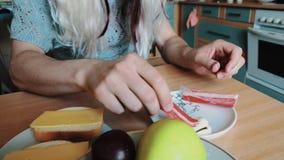 L'uomo nella parrucca del ` s della donna in occhiali da sole mangia i bastoni del granchio alla tavola parody intrattenimento stock footage