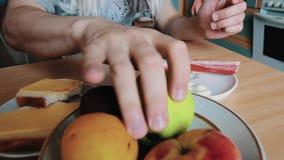 L'uomo nella parrucca del ` s della donna in occhiali da sole mangia il panino e la mela alla tavola parody stock footage