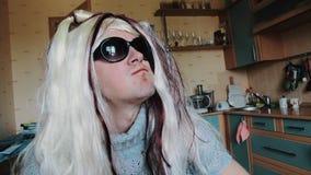 L'uomo nella parrucca del ` s della donna in occhiali da sole mangia la mela alla tavola parody Capelli di tocco masticare video d archivio
