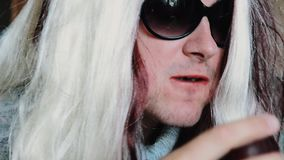 L'uomo nella parrucca del ` s della donna in occhiali da sole mangia la prugna alla tavola parody intrattenimento stock footage