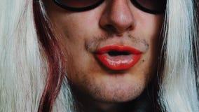 L'uomo nella parrucca della donna in occhiali da sole canta la canzone in camera Pomata rossa sulle labbra parody video d archivio