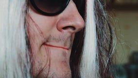 L'uomo nella parrucca della donna in occhiali da sole pronuncia le parole in camera Orli rossi parody stock footage