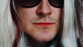 L'uomo nella parrucca della donna in occhiali da sole pronuncia le parole in camera Pomata rossa parody stock footage