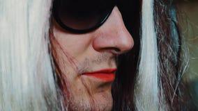 L'uomo nella parrucca della donna in occhiali da sole pronuncia le parole Pomata rossa sulla bocca parody archivi video