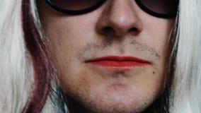 L'uomo nella parrucca della donna in occhiali da sole pronuncia le parole Pomata rossa sulle labbra parody archivi video