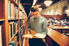 L'uomo nella sala di lettura delle biblioteche ha preso il libro dallo scaffale e dalla lettura immagini stock