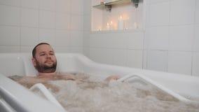 L'uomo nella stazione termale di massaggio nella vasca calda Un uomo nel bagno sta avendo massaggio ricreativo del getto di acqua stock footage