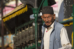 L'uomo nepalese anziano davanti alla preghiera buddista spinge dentro il Nepal, il tempio di Soyambunath, Kathmandu Fotografia Stock Libera da Diritti