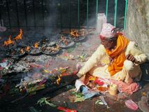 L'uomo nepalese che porta il vestito tradizionale brucia le candele in tempio indù di Dakshinkali in Pharping, Nepal immagine stock libera da diritti