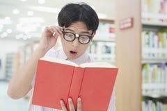 L'uomo nerd con i vetri vede qualche cosa di sorprendente in un libro, in biblioteca immagine stock libera da diritti