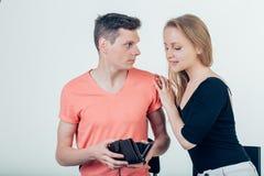 L'uomo nerd sta provando a nascondere i soldi dalla sua moglie perché vuole spenderla tutti fotografie stock libere da diritti