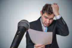 L'uomo nervoso è impaurito di discorso e di sudorazione pubblici Microfono nella parte anteriore fotografie stock libere da diritti
