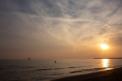 L'uomo nuota all'alba, al sol levante ed alle nuvole immagine stock libera da diritti