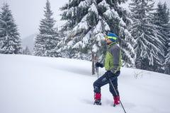L'uomo in occhiali di protezione e racchette da neve sale una collina Immagini Stock Libere da Diritti