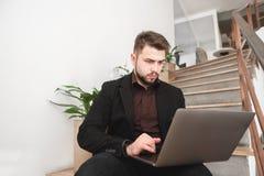 L'uomo occupato si siede sul pavimento contro le scale e le piante e sugli impianti su un computer Copyspace fotografia stock