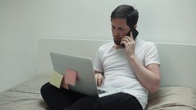 L'uomo occupato sta parlando dal telefono cellulare e sta scrivendo sul computer portatile, sedentesi nella sua camera da letto video d archivio