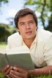 L'uomo osserva alla distanza mentre legge un libro Fotografia Stock