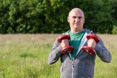 L'uomo ostacola le teste di legno da 5 chili Fotografia Stock
