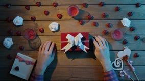 L'uomo ottiene la festa presente in contenitore di regalo dal suo amico, vista superiore video d archivio