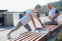 L'uomo ottimistico che guarda la sua moglie fa l'allungamento degli esercizi Fotografia Stock Libera da Diritti