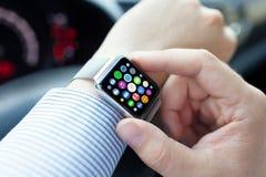 L'uomo passa l'orologio astuto di tocco con i apps delle icone dello schermo domestico Immagine Stock Libera da Diritti