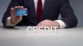 L'uomo passa la carta assegni di credito della tenuta Non pagamento in contanti dalla carta di debito stock footage