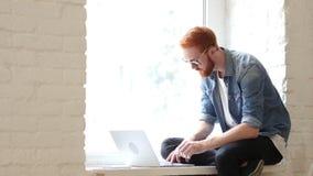 L'uomo pensieroso che lavora online sul computer portatile, scrivere, sedentesi si rilassa in finestra video d archivio