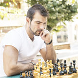 L'uomo pensieroso gioca gli scacchi nel parco. Fotografia Stock