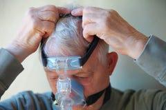 L'uomo più anziano inserisce sopra l'ingranaggio capo del dispositivo di CPAP fotografie stock libere da diritti