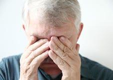 L'uomo più anziano copre gli occhi di mani Fotografia Stock