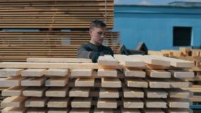 L'uomo piega le plance di legno Pile di plance di legno quadrate per i materiali della mobilia Fucilazione accelerata stock footage