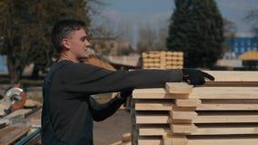 L'uomo piega le plance di legno Pile di plance di legno quadrate per i materiali della mobilia archivi video