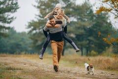 L'uomo porta la sue moglie e figlia sul suo indietro al nex del sentiero nel bosco immagini stock