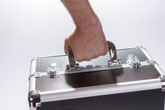 L'uomo porta la valigia di alluminio del metallo Immagine Stock