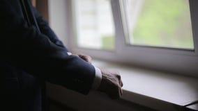 L'uomo porta un rivestimento nel primo mattino nella stanza scura video d archivio