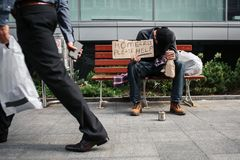 L'uomo povero ed ubriaco sta sedendosi sul banco e tenendo un cartone che dice i senzatetto aiutano prego Ha messo la testa a dis fotografia stock