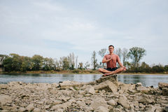 L'uomo pratica l'yoga sulla sponda del fiume Fotografia Stock Libera da Diritti