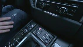 L'uomo preme il bottone sul cruscotto dell'automobile stock footage