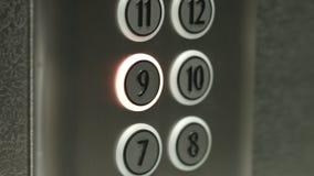 L'uomo preme un bottone il nono pavimento in un elevatore video d archivio