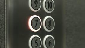 L'uomo preme un bottone il settimo pavimento in un elevatore stock footage
