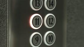 L'uomo preme un bottone l'undicesimo pavimento in un elevatore stock footage