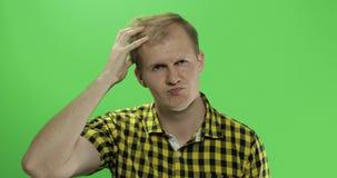 L'uomo premuroso bello in camicia gialla che guarda nella macchina fotografica e pensa stock footage
