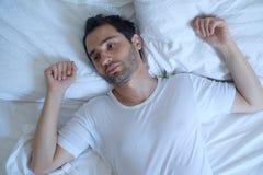 L'uomo premuroso non può dormire a causa di insonnia immagine stock libera da diritti