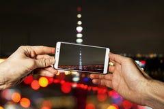 L'uomo prende ad uno smartphone il paesaggio urbano variopinto con una torre della TV immagini stock