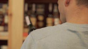 L'uomo prende e mette indietro il cliente del primo piano della bottiglia di vino sta scegliendo la bevanda nel negozio dell'alco archivi video