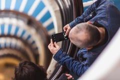 L'uomo prende a foto la vecchia scala a chiocciola blu, scala a spirale dentro una vecchia casa a Budapest, Ungheria Progetto Bud fotografia stock libera da diritti