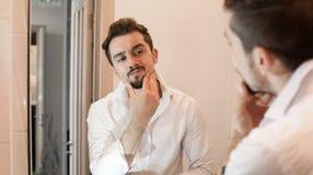 L'uomo prende la cura circa la sua pelle Preoccuparsi in rilievo allegro del tipo della sua pelle Sguardo bello dell'uomo in spec immagine stock libera da diritti