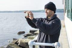 L'uomo prende la foto scenica del telefono cellulare nel porto di Maine Fotografia Stock