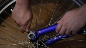 L'uomo prende la ruota fuori dalla bicicletta Sviti il dado con una chiave stock footage